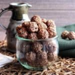Peppermint Chocolate Cookie Dough Bites are filling a large round jar and then is piled as high as it can. The jar is sitting on an open weave mat against a green cloth towel and a pottery pitcher.