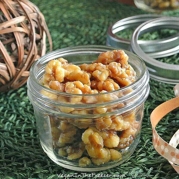 Crock pot Candied Walnuts are in a pint jar with the lid off and a festive ribbon laying the side. Lids are waiting in the background to help decorate the jars.