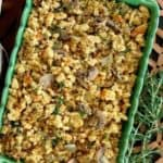 Vegan Sausage Stuffing Casserole is an above head photo and the golden stuffing is in a green casserole on a open weave wooden mat.