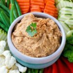 White Bean Dip is in a small bowl and surrounded with piles of colorful fresh sliced veggies.