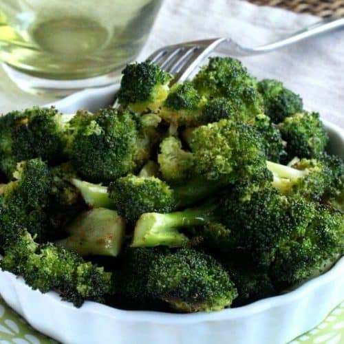 Balsamic Roasted Broccoli is piles high in a whie scalloped serving dish and that is sitting on a green and white printed plate. A fork is piercing a piece and holding it up.