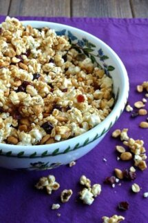 Caramel Popcorn Recipe with Cranberries has a golden color and is spilling out of a bowl ringed in hyacinths. Cranberries, peanuts and popcorn are also on the purple cloth underneath.