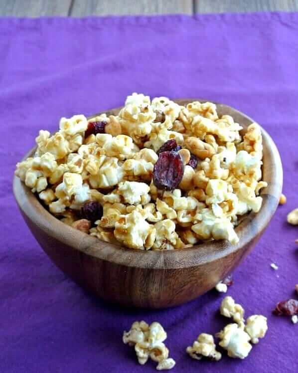 Caramel Popcorn Recipe with Cranberries has a golden color and is spilling out of a small single serve wooden bowl. Cranberries, peanuts and popcorn are also on the purple cloth underneath.