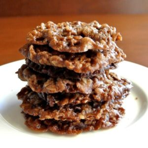 Chocolate Oatmeal Lace Cookies are stacked seven cookies high in a small white plate. Tilted a bit forward to see the lacey cookie pattern