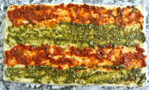Healthy Crescent Roll Pesto Appetizers has one layer of the crescent roll pressed out on a granite cutting board. The two pesto varieties are spread in four stripes across the dough. Waiting to be covered with the other crescent roll layer.