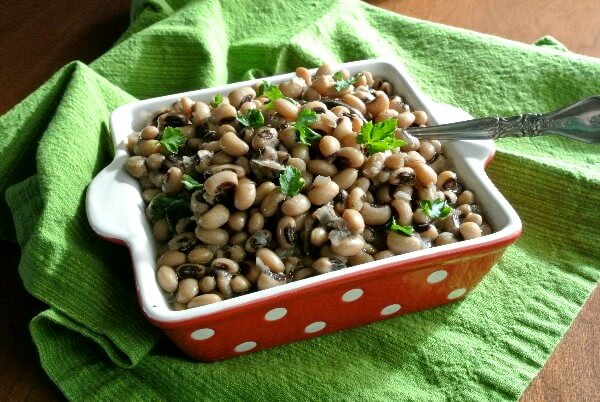 Slow Cooker Black Eyed Peas are filling a red and white polka dot bowl that's sitting on a bright green cloth. Retro festive!