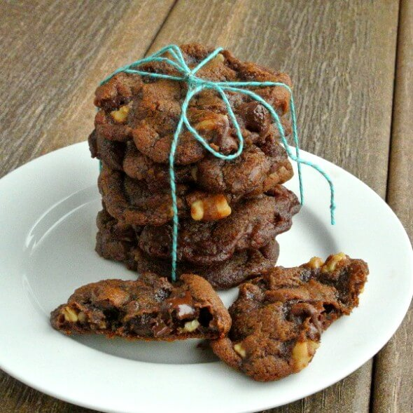 Vegan Chocolate Cookies are stacked five cookie high with a turquoise wrapping string tied in a bow on top. Walnuts showing through the chocolate.
