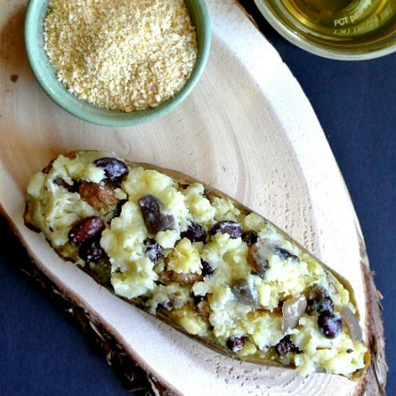 Vegan Stuffed Sweet Potatoes has the photo taken from above. The long sweet potato are sliced in half and is packed full of mixed sweet potatoes, black beans, sauteed onions and so much more. A small green bowl of vegan Parmesan cheese sits alongside.