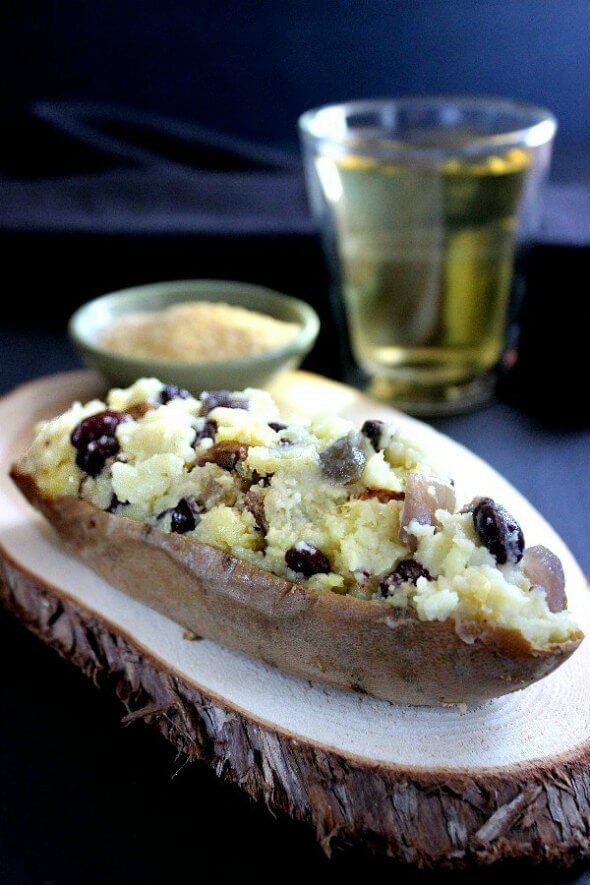 Vegan Stuffed Sweet Potatoes is a close-up side view with mashed sweet potatoes that have been mixed with black beans, sauteed onions and more. Sitting on a sliced board coaster with vegan Parmesan cheese and a glass of chardonnay sitting to the side.
