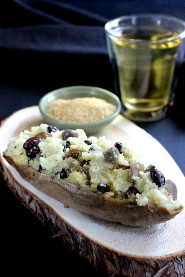 Vegan Stuffed Sweet Potatoes is a half shell stuffed with mashed sweet potatoes that have been mixed with black bean, sauteed onions and more. Sitting on a sliced board coaster with a small green bowl of parmesan cheese sitting behind.