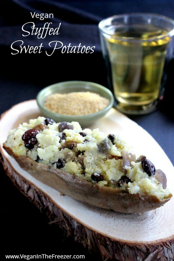Vegan Stuffed Sweet Potatoes is a half shell stuffed with mashed sweet potatoes that have been mixed with black bean, sauteed onions and more. Sitting on a sliced board coaster with a glass of chardonnay sitting to the side.