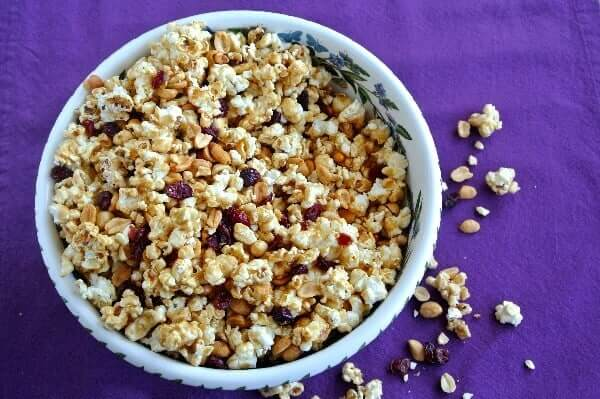 Caramel Popcorn Recipe with Cranberries has a golden color and you are looking down at the bowl full from overhead. Cranberries, peanuts and popcorn are also on the purple cloth underneath.
