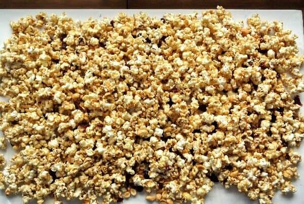 Caramel Popcorn Recipe has just been covered with the caramel topping and is spread out on a parchment paper covered baking sheet. It's an overhead view and the prepared popcorn is ready to be popped in the oven.