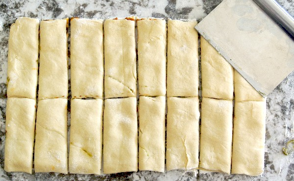 Healthy Crescent Roll Pesto Appetizers are laying on a granite cutting board. The two crescent roll layers are done and a pastry cutter has them sliced into perfect rectangles.