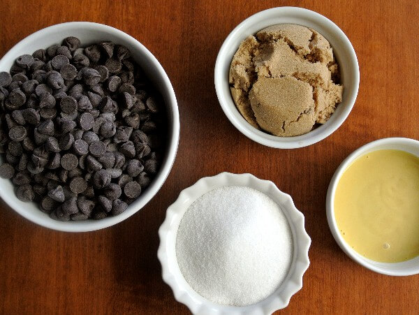 Four of the vegan chocolate cookie ingredients in various shapes and sizes small white bowls.