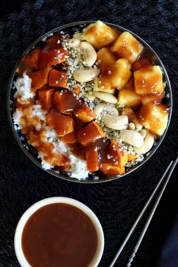 Overhead view of a rice bowl full of veggies and nuts and doused with sweet and sour sauce.