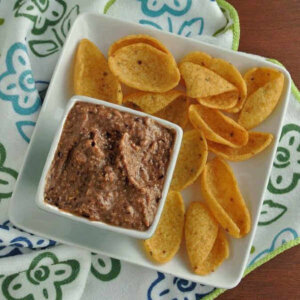 This black bean dip recipe is viewed from overhead and is on a square plate with corn chips.
