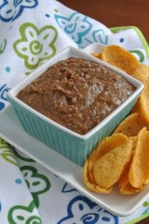 This Black Bean Dip recipe is filling a square turquoise bowl and is being served with Fritos scoops.
