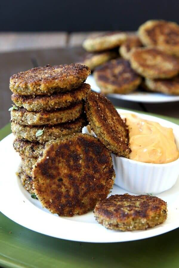 Seven Broccoli Veggie Dippers are stacked high with ones also angled on the stack and in a dipping sauce.