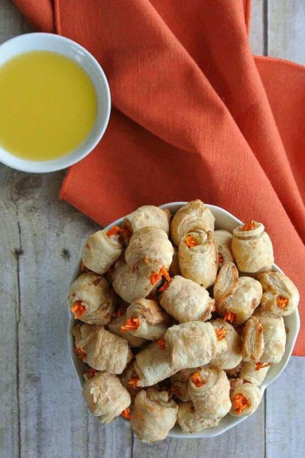 An overhead view of carrot dogs in a blanket filling a bowl with dairy-free melted butter on the side.
