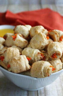 A bowlful of carrot dogs in a blanket are baked golden with tiny strips of carrots sticking out each end.