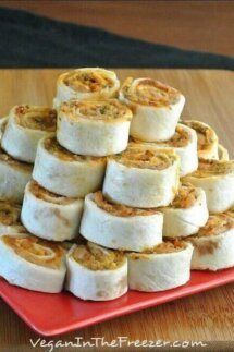 Pesto Tortilla Rollups are stacked in a pyramid shape and are waiting to be eaten.