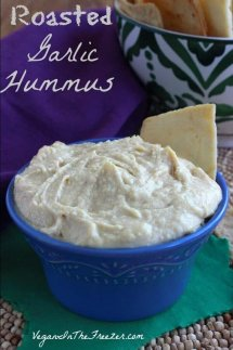 Roasted Garlic Hummus is piled high in a blue bowl set against green and purple.
