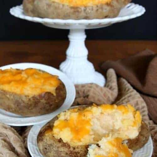 Dairy-Free twice baked potatoes are in a casserole with one on a front plate. A forkful is right in front.