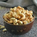 Slow Cooker Spiced Cashews are overflowing a chocolate brown bowl onto a wood beaded mat. Included in 17 Amazing Vegan Appetizers.