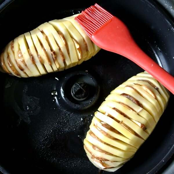 Air Fryer Hasselback& Potatoes in an overhead photo of two potatoes prepared and sitting in an air fryer and a red silicone food brush.