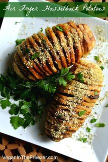 Air Fryer HasselbackPotatoes in an overhead photo on a white square plate and sprinkled with vegan Parmesan and fresh parsley.