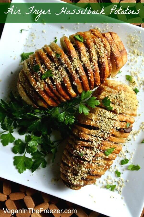 Air Fryer Hasselback Potatoes in an overhead photo on a white square plate and sprinkled with vegan Parmesan and fresh parsley.