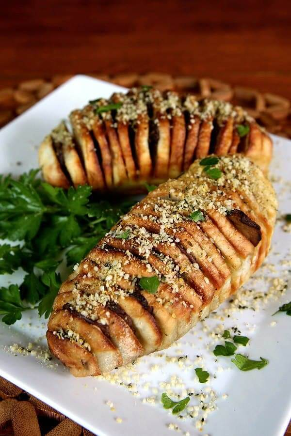 Air Fryer HasselbackPotatoes tilted toward the camera on an angled square plate and sprinkled with vegan Parmesan and fresh parsley.