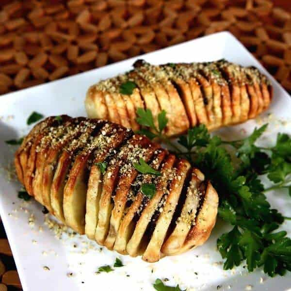 Air Fryer HasselbackPotatoes tilted toward the camera on a square plate and sprinkled with vegan Parmesan and fresh parsley.