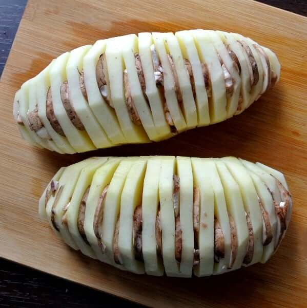Two potatoes are being prepared for Air Fryer Hasselback Potatoes with a thin mushroom slice slid into each potato slice.