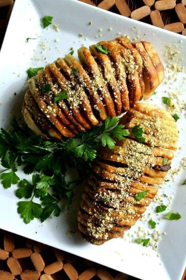 Air Fryer Hasselback Potatoes in an overhead photo on a square plate and sprinkled with vegan parmesan and fresh parsley.