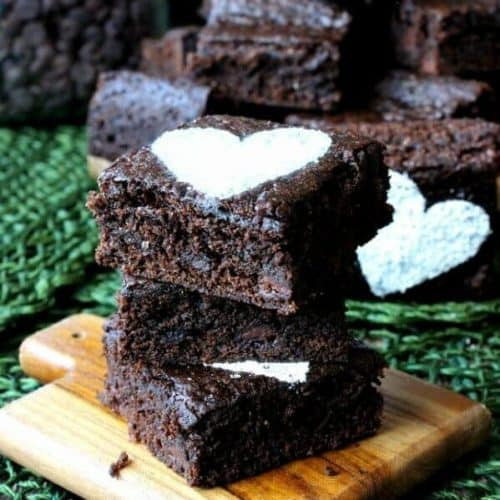 Best Ever Double Chocolate Brownies are stacked three high on a wooden coaster with sugar hearts on top.