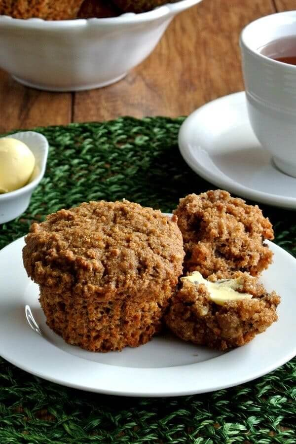 Healthy Morning Muffins are split open and buttered with dairy-free butter on a white plate and green mat. Coffee to the right.
