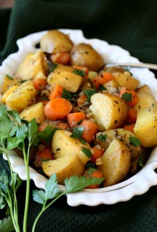 Potatoes and Carrots tilted forward in a white scalloped bowl.