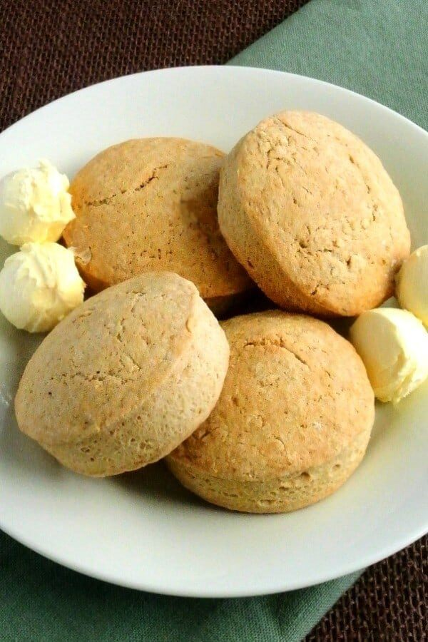 Four big fat Irish Scones are sitting on a plate with four scoops of dairy-free butter.