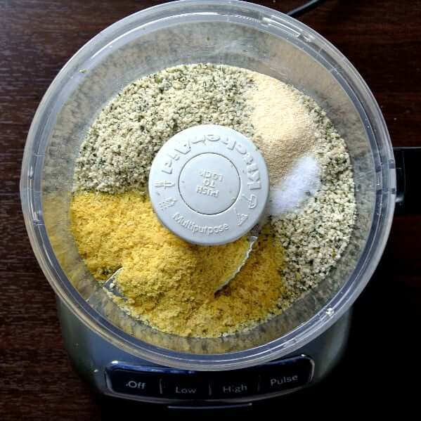 Nut Free Vegan Parmesan Cheese has 5 ingredients and each is in a small white bowl in different shapes.food processor waiting to be combined.