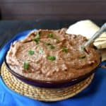 Slow Cooker Refried Beans are piled in a blue bowl with a spooon waiting to dish them up.