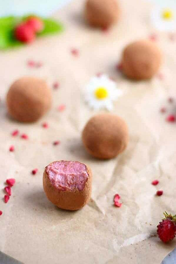 Cocoa covered Vegan Strawberry Truffles spread across parchment with strawberry bits.