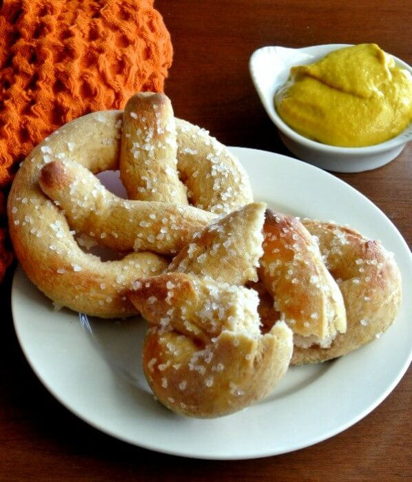 Two homemade soft pretzels are sitting on a small white plate and one is torn in half. Mustard is on the side.