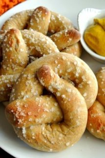 Close-Up photo of soft pillowy homemade giant soft pretzels. A little bit of mustard is in the corner.