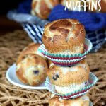Three of the best mini blueberry muffins stacked three high on a open woven straw met with a silver basket full of more behind.