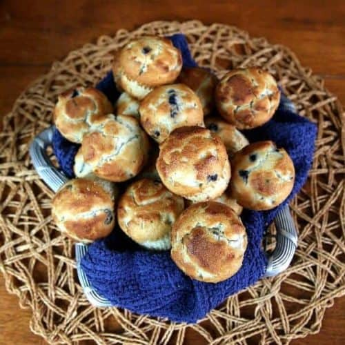 Silver metal basket is draped in cobalt with the best mini blueberry muffins piled high.