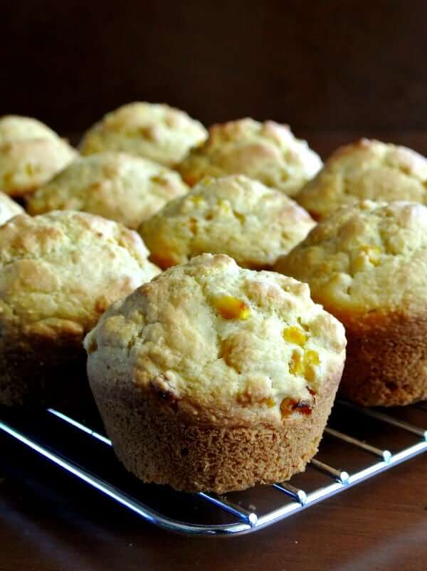 Vegan Cornbread Muffins sitting on a cooling rack with one front and center.