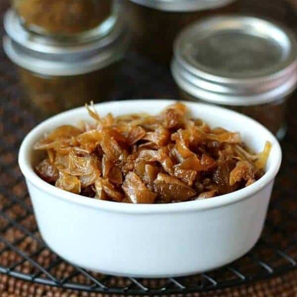 Glistening golden slow cooker caramelized onions are filling a small white bowl with half pint canning jars stacked filled and stacked behind.