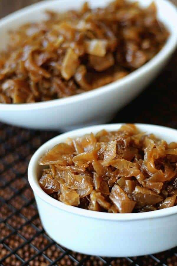 Close up photo of two white bowls filled with glistening golden slow cooker caramelized onions.